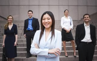 Being Youthanized-Young Professional Woman standing with team smiling
