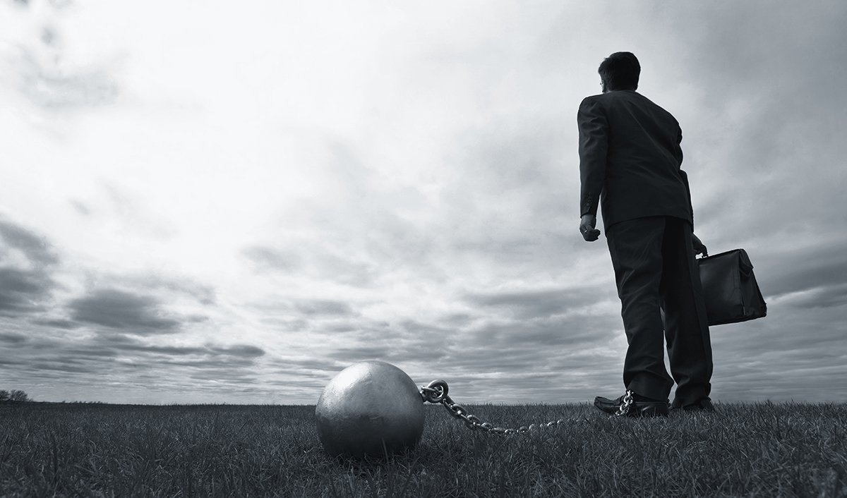 Duty or Desire-Nesso Strategies-Businessman with ball and chain looking into the distance