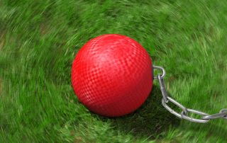 Kickball Chains-Red kickball with thick silver chain attached on a grass