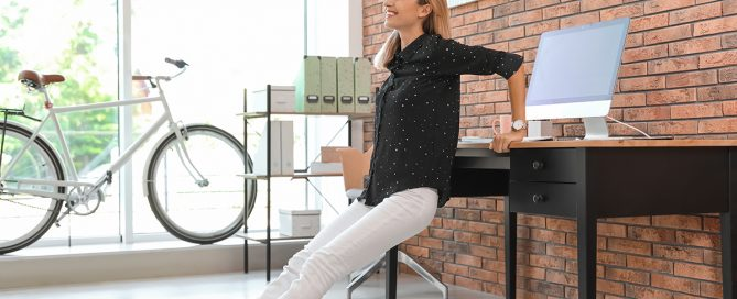 Keep It Moving-Young businesswoman stretching at workplace. Productivity boost