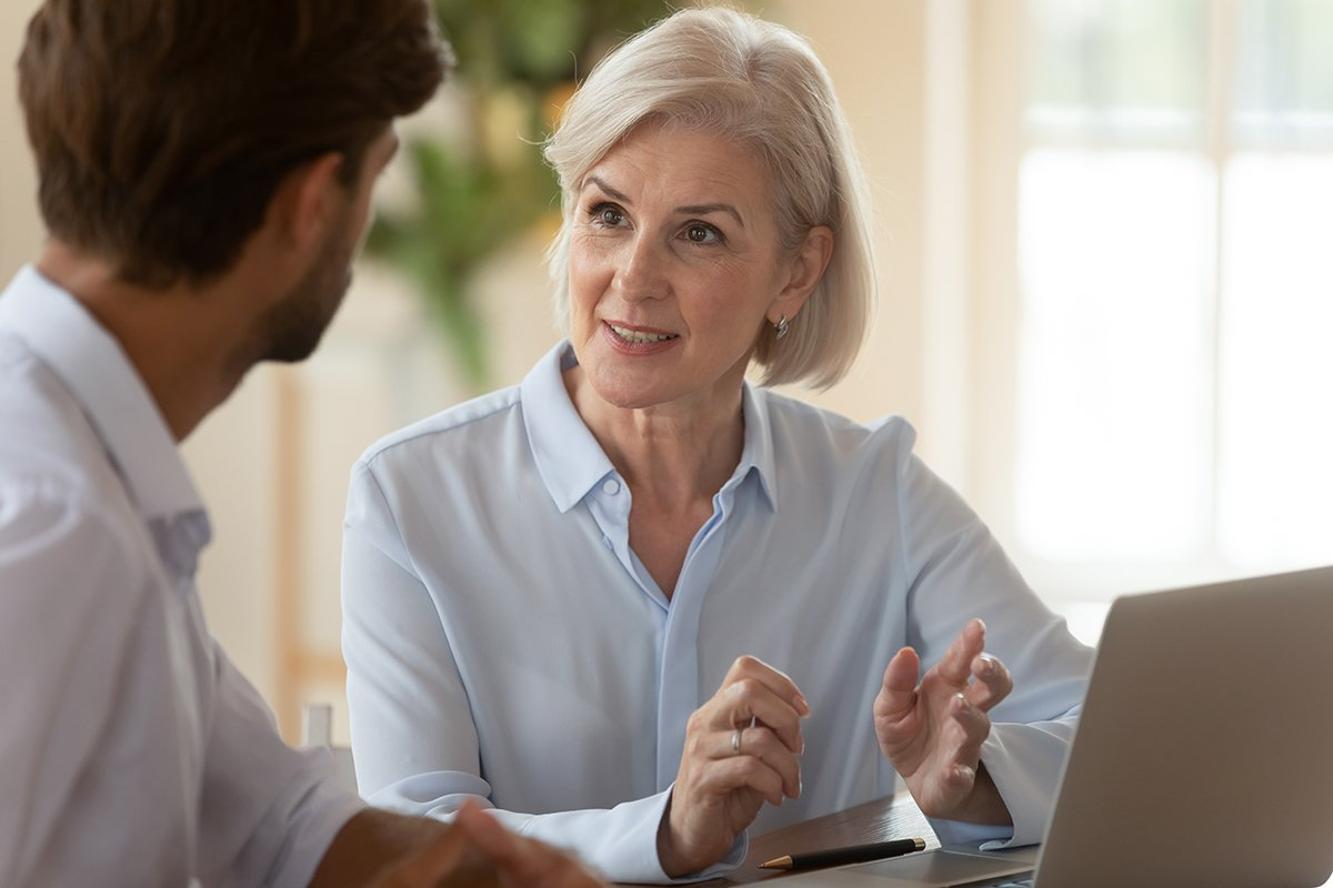 Lets Get Personal-Middle aged businesswoman manager speaking to businessman client teaching intern
