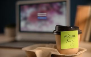 Build the Plan Stan-welcome coffee cup and laptop on desk
