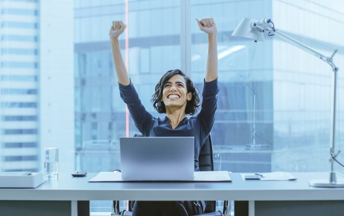 Play to Win or Not Lose-Triumphant Businesswoman at desk arms raised