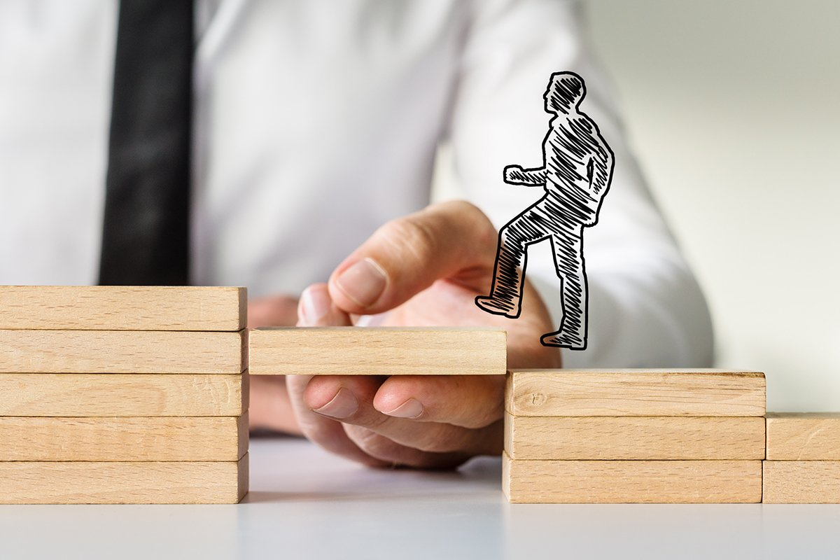 Wide view image of hand drawn shape of a businessman walking up the wooden steps supported by male hand. Conceptual of business coaching