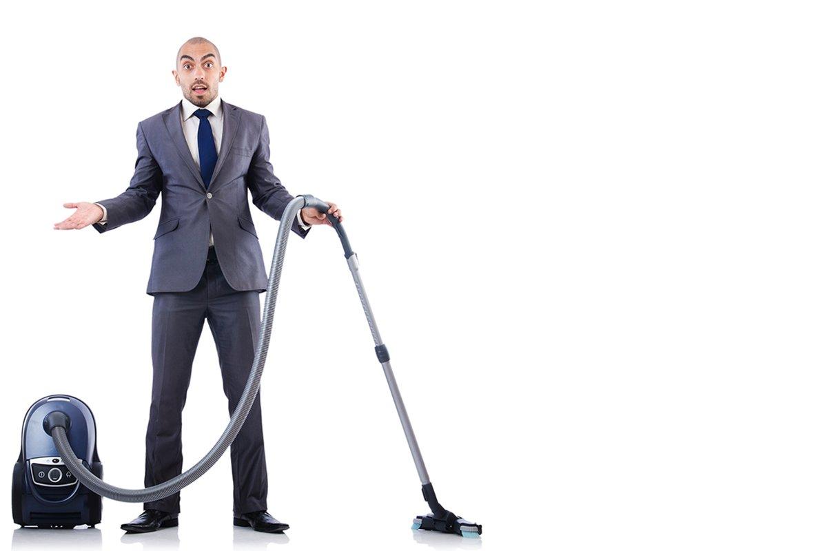Businessman vacuuming looking confused
